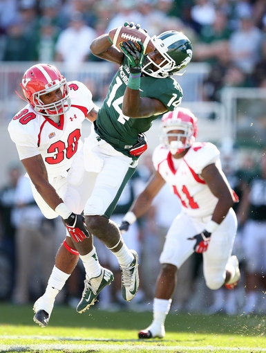 Sep 14, 2013; East Lansing, MI, USA; Michigan State Spartans wide receiver Tony Lippett (14) catches a pass against Youngstown State Penguins safety Tre' Moore (30) during the second half in a game at Spartan Stadium. MSU won 55-17.Mandatory Credit: Mike Carter-USA TODAY Sports