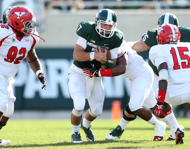 Sep 14, 2013; East Lansing, MI, USA; Michigan State Spartans quarterback Tyler O'Connor (7) runs for first down against the Youngstown State Penguins during the second half in a game at Spartan Stadium. MSU won 55-17.Mandatory Credit: Mike Carter-USA TODAY Sports