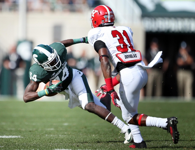 Sep 14, 2013; East Lansing, MI, USA; Michigan State Spartans wide receiver Tony Lippett (14) is tripped up by Youngstown State Penguins cornerback David Rivers (31) during the second half in a game at Spartan Stadium. MSU won 55-17.Mandatory Credit: Mike Carter-USA TODAY Sports