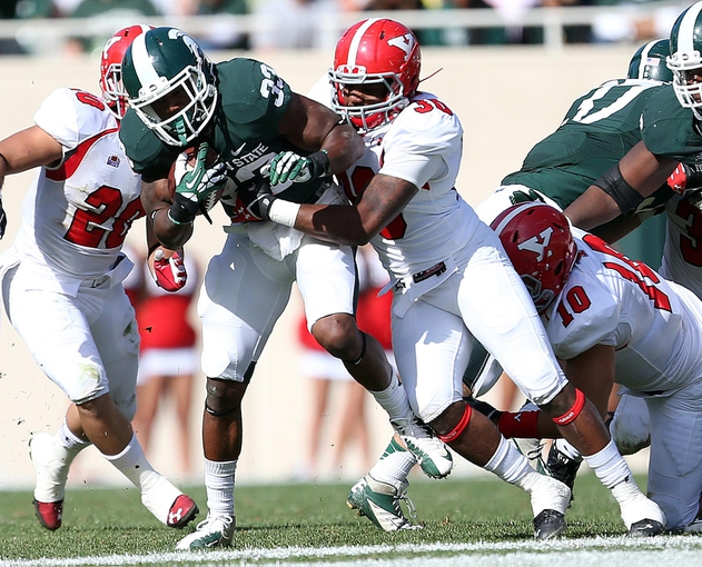 Sep 14, 2013; East Lansing, MI, USA;Michigan State Spartans running back Jeremy Langford (33) is tackled by Youngstown State Penguins safety Tre' Moore (30) during the second half in a game at Spartan Stadium. MSU won 55-17.Mandatory Credit: Mike Carter-USA TODAY Sports