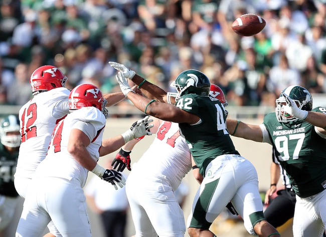 Sep 14, 2013; East Lansing, MI, USA; Youngstown State Penguins quarterback Kurt Hess (12) is hurried by Michigan State Spartans defensive end Denzel Drone (42) during the second half in a game at Spartan Stadium. MSU won 55-17.Mandatory Credit: Mike Carter-USA TODAY Sports