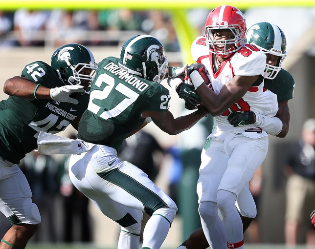 Sep 14, 2013; East Lansing, MI, USA; Youngstown State Penguins wide receiver Andrew Williams (80) is wrapped up by Michigan State Spartans safety Kurtis Drummond (27) during the second half in a game at Spartan Stadium. MSU won 55-17.Mandatory Credit: Mike Carter-USA TODAY Sports
