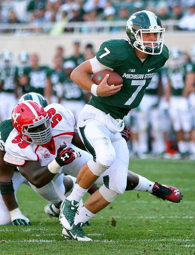 Sep 14, 2013; East Lansing, MI, USA; Michigan State Spartans quarterback Tyler O'Connor (7) runs for a first down against the Youngstown State Penguins during the second half in a game at Spartan Stadium. MSU won 55-17. Mandatory Credit: Mike Carter-USA TODAY Sports