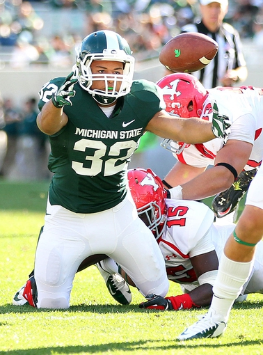 Sep 14, 2013; East Lansing, MI, USA; Michigan State Spartans running back Nick Tompkins (32) fumbles the ball against the Youngstown State Penguins during the second half in a game at Spartan Stadium. MSU won 55-17. Mandatory Credit: Mike Carter-USA TODAY Sports