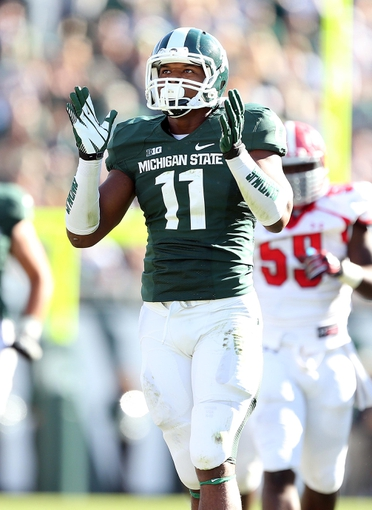 Sep 14, 2013; East Lansing, MI, USA; Michigan State Spartans defensive end Jamal Lyles (11) celebrates a touchdown against the Youngstown State Penguins during the second half in a game at Spartan Stadium. MSU won 55-17. Mandatory Credit: Mike Carter-USA TODAY Sports