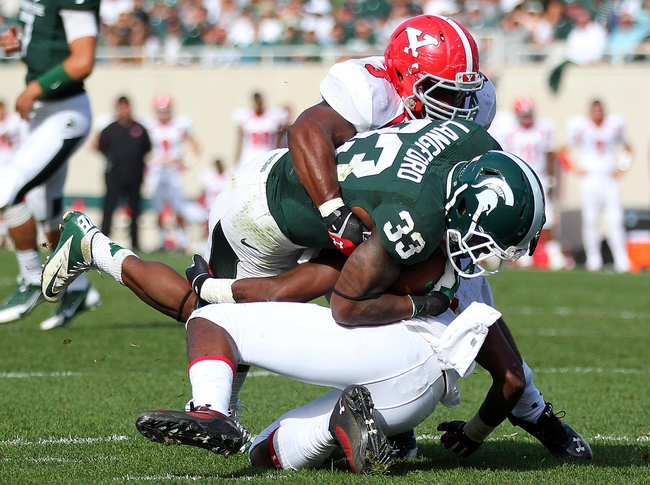 Sep 14, 2013; East Lansing, MI, USA; Michigan State Spartans running back Jeremy Langford (33) is stopped short of the goal line by Youngstown State Penguins safety Tre' Moore (30) during the second half in a game at Spartan Stadium. MSU won 55-17. Mandatory Credit: Mike Carter-USA TODAY Sports