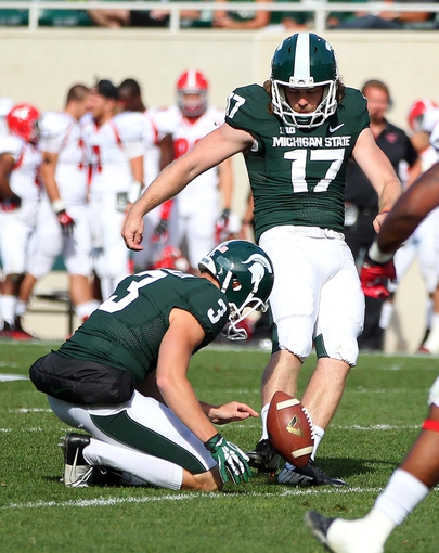 Sep 14, 2013; East Lansing, MI, USA; Michigan State Spartans kicker Kevin Muma (17) kicks a field goal out of the hold by punter Mike Sadler (3) during the second half in a game against the Youngstown State Penguins at Spartan Stadium. MSU won 55-17. Mandatory Credit: Mike Carter-USA TODAY Sports