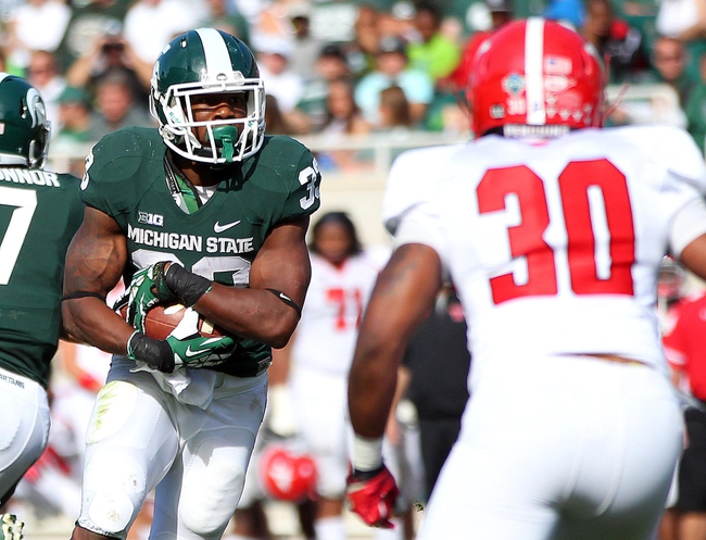 Sep 14, 2013; East Lansing, MI, USA; Michigan State Spartans running back Jeremy Langford (33) runs the ball  against Youngstown State Penguins safety Tre' Moore (30) during the second half in a game at Spartan Stadium. MSU won 55-17. Mandatory Credit: Mike Carter-USA TODAY Sports