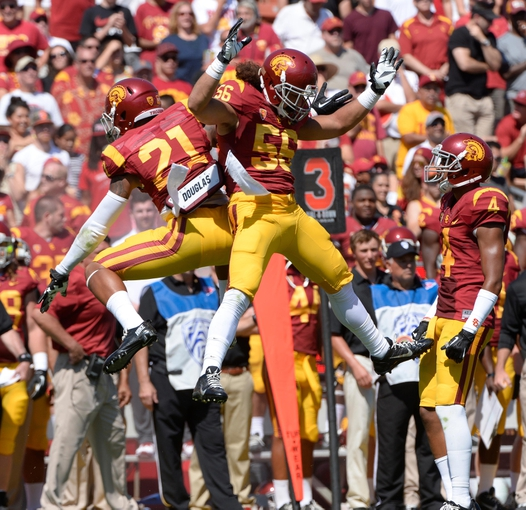 Sep 14, 2013; Los Angeles, CA, USA; USC Trojans safety Su'a Cravens (21) and linebacker Anthony Sarao (56) celebrate stopping Boston College Eagles quarterback Chase Rettig (not pictured) short of a first down during the third quarter  at Los Angeles Memorial Coliseum. USC went on to a 35-7 win.