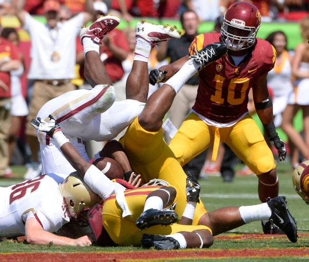 Sep 14, 2013; Los Angeles, CA, USA; Boston College Eagles running back Andre Williams (44) is flipped upside down as he is tackled by members of the USC Trojans defense during the game at Los Angeles Memorial Coliseum.