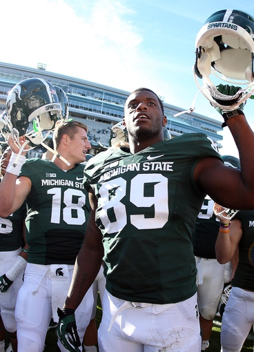 Sep 14, 2013; East Lansing, MI, USA; Michigan State Spartans quarterback Connor Cook (18) and defensive end Shilique Calhoun (89) celebrate after the game against the Youngstown State Penguins at Spartan Stadium. MSU won 55-17.Mandatory Credit: Mike Carter-USA TODAY Sports