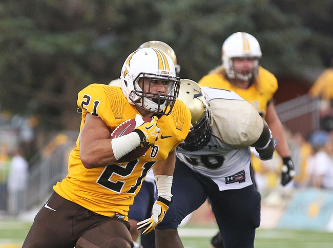 Sep 14, 2013; Laramie, WY, USA; Wyoming Cowboys running back Shaun Wick (21) runs for a touchdown against Northern Colorado Bears linebacker Clarence Bumpas (56) during the fourth quarter at War Memorial Stadium. Mandatory Credit: Troy Babbitt-USA TODAY Sports