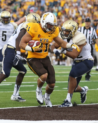 Sep 14, 2013; Laramie, WY, USA; Wyoming Cowboys running back Shaun Wick (21) runs for a touchdown against Northern Colorado Bears safety Kyle Griffin (42) during the fourth quarter at War Memorial Stadium. Mandatory Credit: Troy Babbitt-USA TODAY Sports