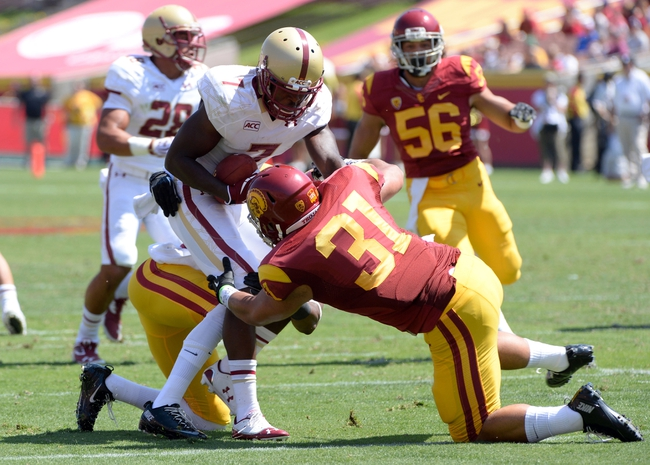 Sep 14, 2013; Los Angeles, CA, USA; Boston College Eagles wide receiver Spiffy Evans (7) is tackled by USC Trojans cornerback Kevon Seymour (13) and Soma Vainuku (31) during a first half kick off  at Los Angeles Memorial Coliseum. The Trojans went on to a 35-7 win.