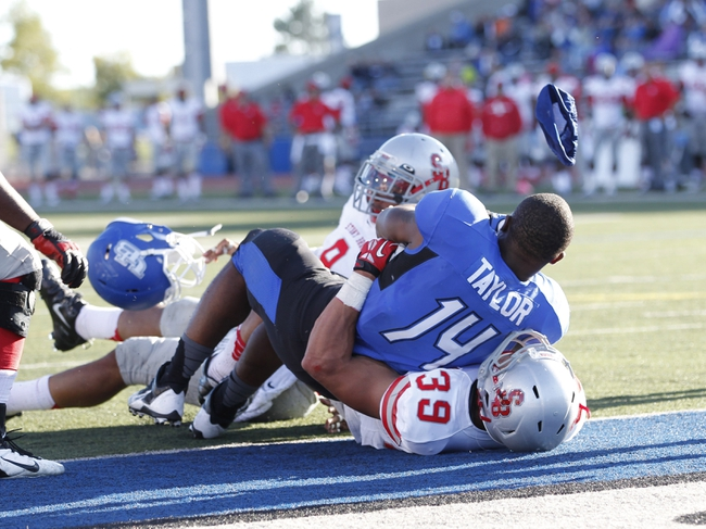 Sep 14, 2013; Buffalo, NY, USA; Buffalo Bulls running back Anthone Taylor (14) scores a touchdown and loses his helmet during the second half against the Stony Brook Seawolves at University of Buffalo Stadium. Buffalo beats Stony Brook 26-23 in OT. Mandatory Credit: Kevin Hoffman-USA TODAY Sports
