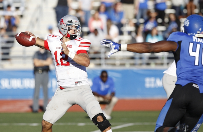 Sep 14, 2013; Buffalo, NY, USA; Stony Brook Seawolves quarterback Lyle Negron (12) drops to pass as Buffalo Bulls linebacker Khalil Mack (46) rushes during the second half at University of Buffalo Stadium. Buffalo beats Stony Brook 26-23 in OT. Mandatory Credit: Kevin Hoffman-USA TODAY Sports