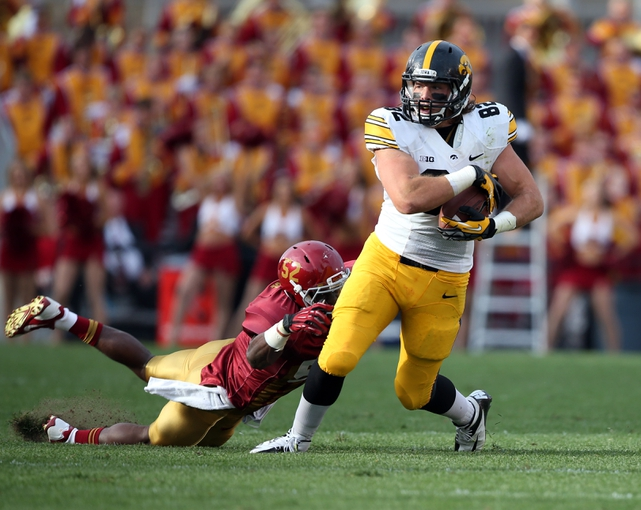 September 14, 2013; Ames, IA, USA;  Iowa State Cyclones linebacker Jeremiah George (52) grabs a hold of Iowa Hawkeyes tight end Ray Hamilton (82) in the first quarter at Jack Trice Stadium. Mandatory Credit: Reese Strickland-US PRESSWIRE