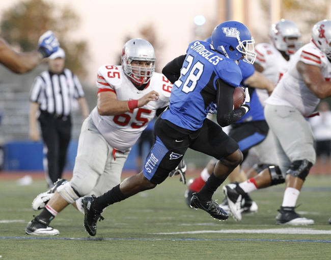 Sep 14, 2013; Buffalo, NY, USA; Buffalo Bulls defensive back Dwellie Striggles (28) intercepts a pass in OT as Stony Brook Seawolves offensive linesman Mike Lisi (65) pursues at University of Buffalo Stadium. Buffalo beats Stony Brook 26-23 in OT. Mandatory Credit: Kevin Hoffman-USA TODAY Sports