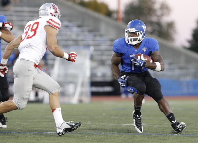 Sep 14, 2013; Buffalo, NY, USA; Buffalo Bulls running back Anthone Taylor (14) runs as Stony Brook Seawolves defensive back Christian Ricard (39) pursues in OT at University of Buffalo Stadium. Buffalo beats Stony Brook 26-23 in OT. Mandatory Credit: Kevin Hoffman-USA TODAY Sports