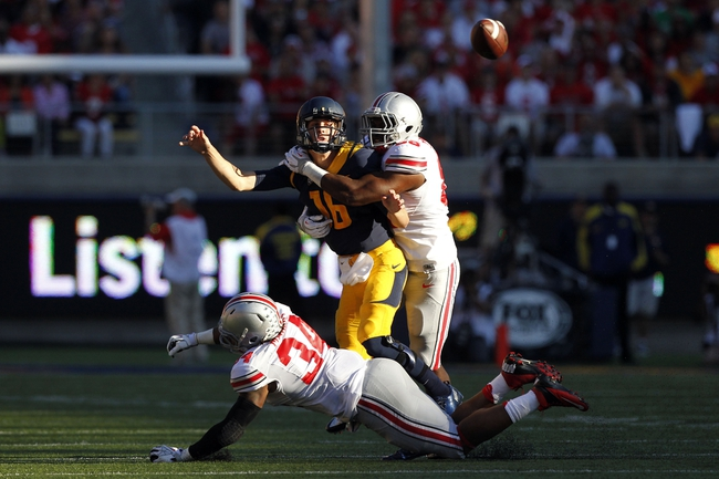Sep 14, 2013; Berkeley, CA, USA; California Golden Bears quarterback Jared Goff (16) is hit by Ohio State Buckeyes defensive lineman Jamal Marcus (34) and defensive lineman Steve Miller (88) in the second quarter at Memorial Stadium. Mandatory Credit: Cary Edmondson-USA TODAY Sports