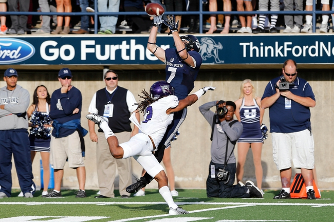 Sep 14, 2013; Logan, UT, USA; Utah State Aggies wide receiver Travis Van Leeuwen (7) jumps over Weber State Wildcats quarterback Jonathan Willis (3) to catch the ball during the first quarter at Romney Stadium. Mandatory Credit: Chris Nicoll-USA TODAY Sports