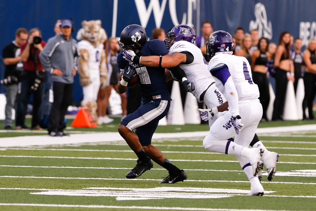 Sep 14, 2013; Logan, UT, USA; Utah State Aggies wide receiver Brandon Swindall (11) has his face mask pulled on by Weber State Wildcats linebacker Anthony Morales (44) during the first quarter at Romney Stadium. Mandatory Credit: Chris Nicoll-USA TODAY Sports