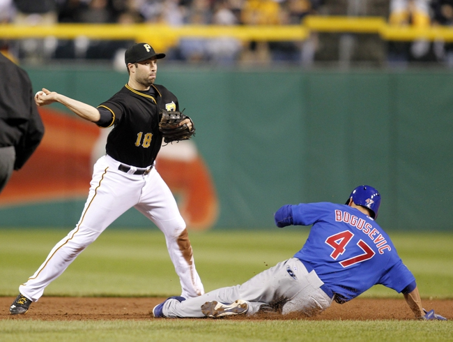 Sep 14, 2013; Pittsburgh, PA, USA; Pittsburgh Pirates second baseman Neil Walker (18) turns a game ending double play over Chicago Cubs right fielder Brian Bogusevic (47) during the ninth inning at PNC Park. The Pittsburgh Pirates won 2-1. Mandatory Credit: Charles LeClaire-USA TODAY Sports