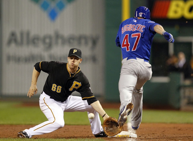 Sep 14, 2013; Pittsburgh, PA, USA; Chicago Cubs right fielder Brian Bogusevic (47) reaches first base on a passed ball after striking out as Pittsburgh Pirates first baseman Justin Morneau (66) reaches for the throw during the ninth inning at PNC Park. The Pittsburgh Pirates won 2-1. Mandatory Credit: Charles LeClaire-USA TODAY Sports