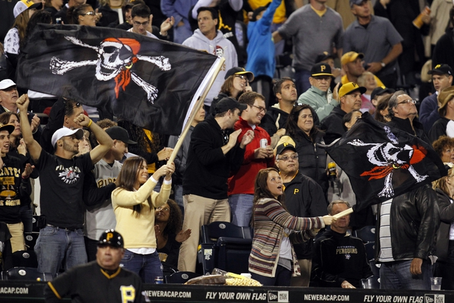Sep 14, 2013; Pittsburgh, PA, USA; Pittsburgh Pirates fans wave Jolly Roger flags as they cheer against the Chicago Cubs during the seventh inning stretch at PNC Park. The Pittsburgh Pirates won 2-1. Mandatory Credit: Charles LeClaire-USA TODAY Sports