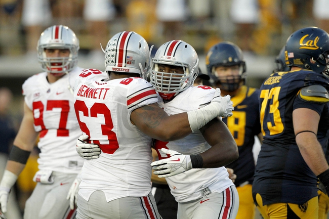 Sep 14, 2013; Berkeley, CA, USA; Ohio State Buckeyes defensive lineman Noah Spence (8) is congratulated by defensive lineman Michael Bennett (63) after sacking California Golden Bears quarterback Jared Goff (not pictured) in the third quarter at Memorial Stadium. The Buckeyes defeated the Golden Bears 52-34. Mandatory Credit: Cary Edmondson-USA TODAY Sports