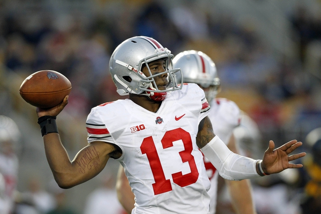 Sep 14, 2013; Berkeley, CA, USA; Ohio State Buckeyes quarterback Kenny Guiton (13) prepares to throw a pass against the California Golden Bears in the fourth quarter at Memorial Stadium. The Buckeyes defeated the Golden Bears 52-34. Mandatory Credit: Cary Edmondson-USA TODAY Sports
