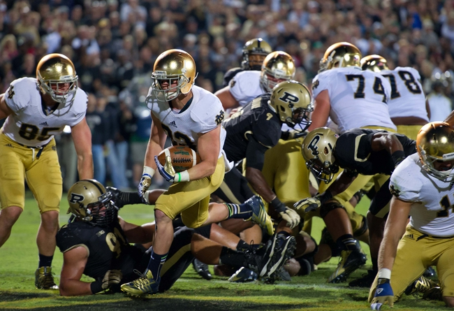 Sep 14, 2013; West Lafayette, IN, USA; Notre Dame Fighting Irish running back Cam McDaniel (33) runs into the end zone for a touchdown as Purdue Boilermakers defensive end Greg Latta (91) defends in the third quarter at Ross-Ade Stadium. Notre Dame won 31-24. Mandatory Credit: Matt Cashore-USA TODAY Sports