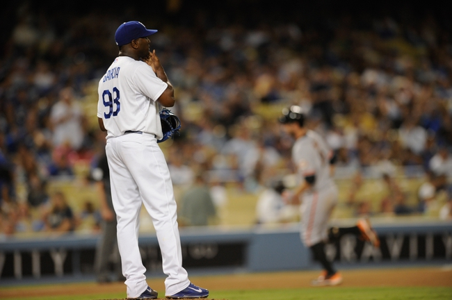 Sep 14, 2013; Los Angeles, CA, USA; Los Angeles Dodgers pitcher Onelki Garcia reacts after giving up a two run home run to San Francisco Giants first baseman Brandon Belt (back) during the seventh inning at Dodger Stadium. Mandatory Credit: Kelvin Kuo-USA TODAY Sports