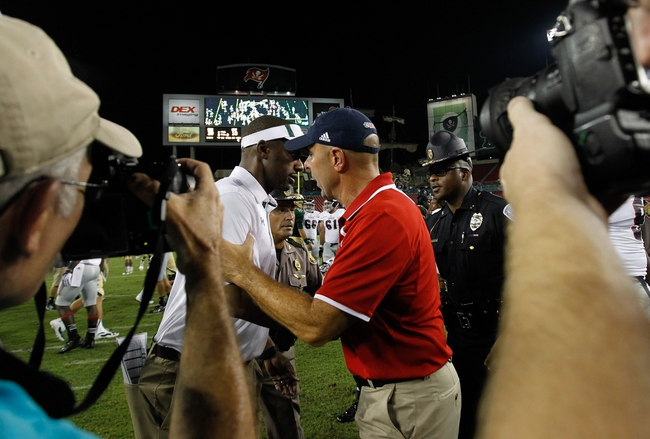 Sep 14, 2013; Tampa, FL, USA; South Florida Bulls head coach Willie Taggart and Florida Atlantic Owls head coach Carl Pelini greet at the end of the game at Raymond James Stadium. Florida Atlantic Owls defeated the South Florida Bulls 28-10. Mandatory Credit: Kim Klement-USA TODAY Sports