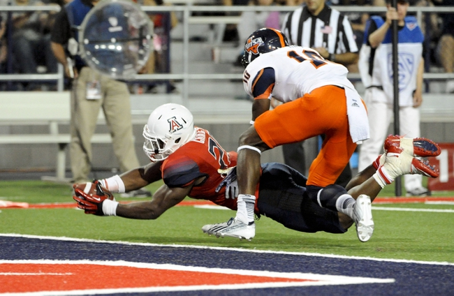 Sep 14, 2013; Tucson, AZ, USA; Arizona Wildcats running back KaDeem Carey (25) scores a touchdown as he is pursued by Texas-San Antonio Roadrunners safety Brian King (10) during the fourth quarter at Arizona Stadium. The Wildcats defeated the Roadrunners 38-13. Mandatory Credit: Casey Sapio-USA TODAY Sports