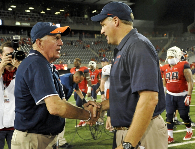 Sep 14, 2013; Tucson, AZ, USA; Texas-San Antonio Roadrunners head coach Larry Coker and Arizona Wildcats head coach Rich Rodriguez shake hands after the fourth quarter at Arizona Stadium. The Wildcats defeated the Roadrunners 38-13. Mandatory Credit: Casey Sapio-USA TODAY Sports