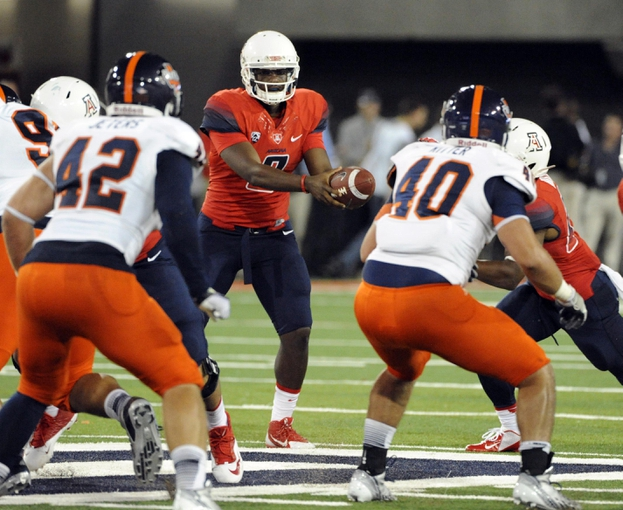 Sep 14, 2013; Tucson, AZ, USA; Arizona Wildcats quarterback Javelle Allen (9) hands the ball off during the fourth quarter against the Texas-San Antonio Roadrunners at Arizona Stadium. The Wildcats defeated the Roadrunners 38-13. Mandatory Credit: Casey Sapio-USA TODAY Sports
