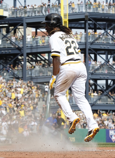 Sep 15, 2013; Pittsburgh, PA, USA; Pittsburgh Pirates center fielder Andrew McCutchen (22) reacts after sliding across home plate with the game winning run against the Chicago Cubs during the eighth inning at PNC Park. The Pittsburgh Pirates won 3-2. Mandatory Credit: Charles LeClaire-USA TODAY Sports