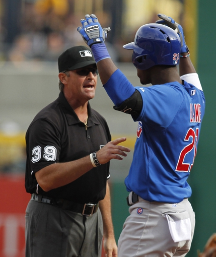Sep 15, 2013; Pittsburgh, PA, USA; Chicago Cubs left fielder Junior Lake (21) reacts after being called out at first base by umpire Paul Nauert (39) against the Pittsburgh Pirates during the ninth inning at PNC Park. The Pittsburgh Pirates won 3-2. Mandatory Credit: Charles LeClaire-USA TODAY Sports