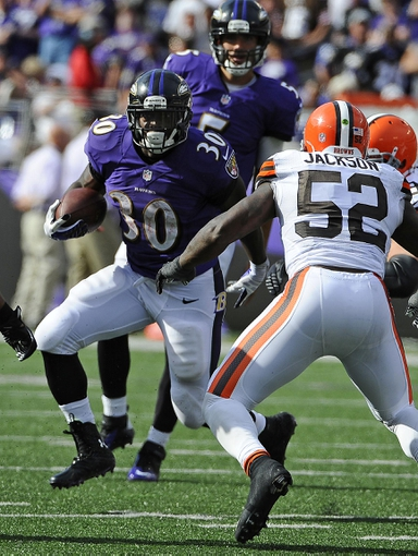 Sep 15, 2013; Baltimore, MD, USA; Baltimore Ravens running back Bernard Pierce (30) runs with the ball against Cleveland Browns linebacker D'Qwell Jackson (52) during the second half at M&T Bank Stadium. The Ravens won 14 - 6. Mandatory Credit: Brad Mills-USA TODAY Sports