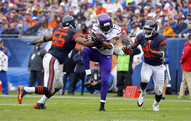 Sep 15, 2013; Chicago, IL, USA; Minnesota Vikings wide receiver Jarius Wright (center) catches a pass between Chicago Bears outside linebacker Lance Briggs (left) and cornerback Charles Tillman (right) during the second half at Soldier Field. Chicago won 31-30. Mandatory Credit: Dennis Wierzbicki-USA TODAY Sports