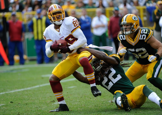 Sep 15, 2013; Green Bay, WI, USA;  Washington Redskins wide receiver Santana Moss (89) is tackled by Green Bay Packers safety Jerron McMillian (22) after a short gain in the fourth quarter at Lambeau Field. Mandatory Credit: Benny Sieu-USA TODAY Sports