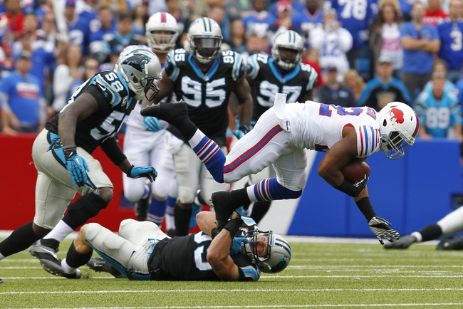 Sep 15, 2013; Orchard Park, NY, USA; Buffalo Bills running back Fred Jackson (22) gets tackled by Carolina Panthers middle linebacker Luke Kuechly (59) during the second half at Ralph Wilson Stadium. Buffalo beats Carolina 27 to 26.  Mandatory Credit: Timothy T. Ludwig-USA TODAY Sports
