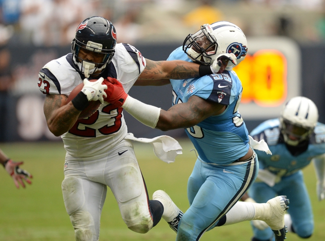 Sep 15, 2013; Houston, TX, USA; Houston Texans running back Arian Foster (23) stiff arms Tennessee Titans outside linebacker Zach Brown (55)during overtime at Reliant Stadium. The Texans won 30-24. Mandatory Credit: Thomas Campbell-USA TODAY Sports