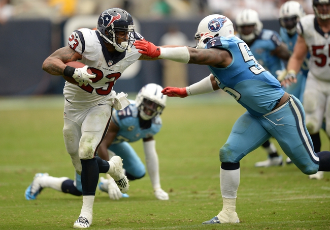 Sep 15, 2013; Houston, TX, USA; Houston Texans running back Arian Foster (23) stiff arms Tennessee Titans outside linebacker Zach Brown (55) during overtime at Reliant Stadium. The Texans won 30-24. Mandatory Credit: Thomas Campbell-USA TODAY Sports