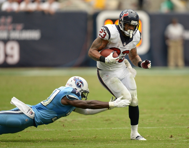 Sep 15, 2013; Houston, TX, USA; Houston Texans running back Arian Foster (23) rushes past Tennessee Titans cornerback Jason McCourty (30) during overtime at Reliant Stadium. The Texans won 30-24. Mandatory Credit: Thomas Campbell-USA TODAY Sports