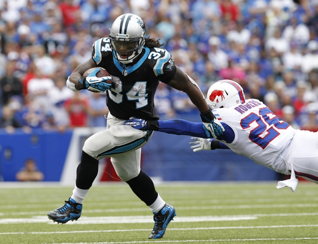 Sep 15, 2013; Orchard Park, NY, USA; Carolina Panthers running back DeAngelo Williams (34) breaks a tackle by Buffalo Bills defensive back Justin Rogers (26) during the second half at Ralph Wilson Stadium. Buffalo beat Carolina 27-26. Mandatory Credit: Kevin Hoffman-USA TODAY Sports