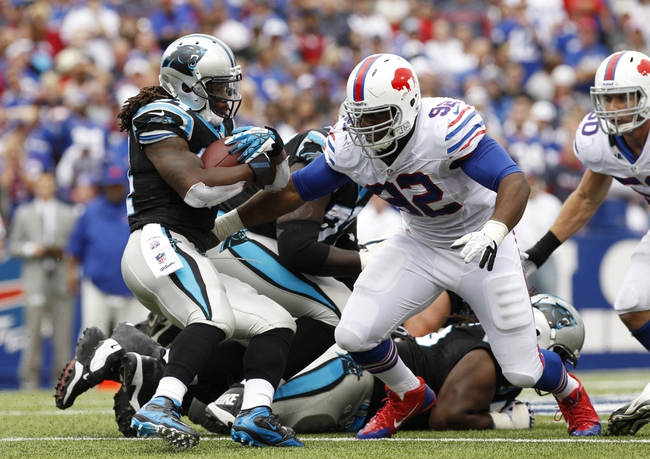 Sep 15, 2013; Orchard Park, NY, USA; Carolina Panthers running back DeAngelo Williams (34) is tackled by Buffalo Bills defensive end Alex Carrington (92) during the second half at Ralph Wilson Stadium. Buffalo beat Carolina 27-26. Mandatory Credit: Kevin Hoffman-USA TODAY Sports