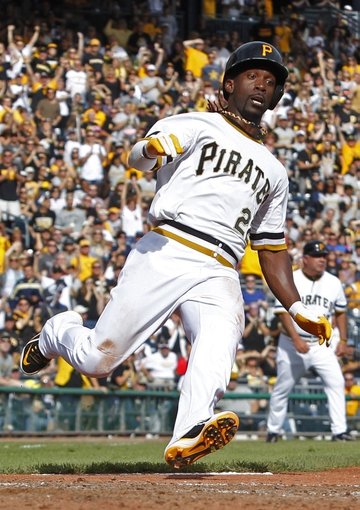 Sep 15, 2013; Pittsburgh, PA, USA; Pittsburgh Pirates center fielder Andrew McCutchen (22) begins his slide across home plate with the game winning run against the Chicago Cubs during the eighth inning at PNC Park. The Pittsburgh Pirates won 3-2. Mandatory Credit: Charles LeClaire-USA TODAY Sports