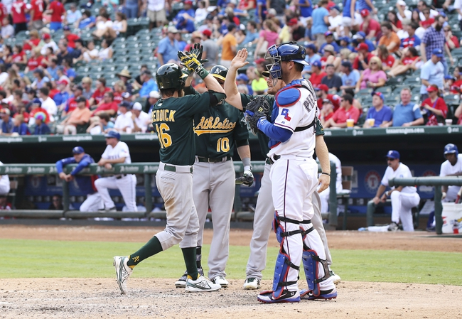 Sep 15, 2013; Arlington, TX, USA; Oakland Athletics right fielder Josh Reddick (16) celebrates with first baseman Daric Barton (10) and first baseman Brandon Moss (right) after hitting a home run as Texas Rangers catcher A.J. Pierzynski (12) looks on during the ninth inning at Rangers Ballpark in Arlington. Mandatory Credit: Kevin Jairaj-USA TODAY Sports